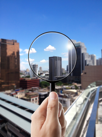 view: Magnifying glass and cityscape in focus, business vision