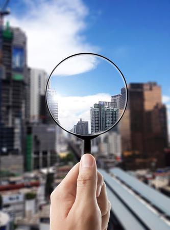 Увеличительное стекло и городской пейзаж в центре внимания, видение бизнеса