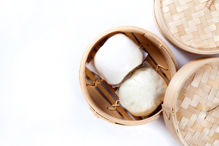 Steamed buns in bamboo steamer on white background, chinese dim sum