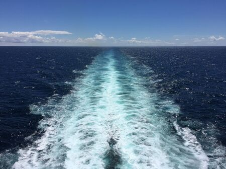 A ship's wake as it cruises out in the middle of the ocean