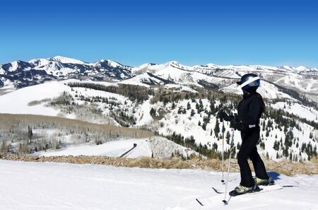 A skier enjoying the view on top of a snow capped mountain in Deer Valley Utah