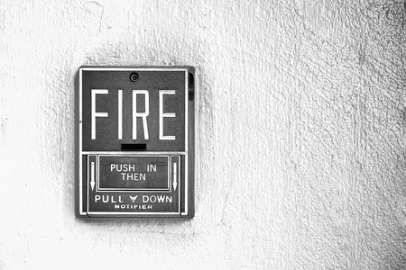 finger on trigger: Fire alarm button on the wall black and white Stock Photo