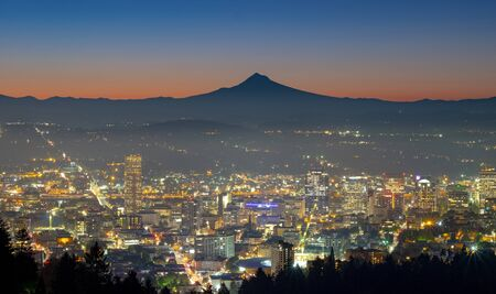 Downtown Portland Oregon lit up in the darkness with Mount Hood in the distance.