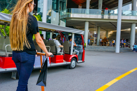 Young woman with long hairs on electric scooter. The girl on the electric scooter drinks coffee. Stock Photo