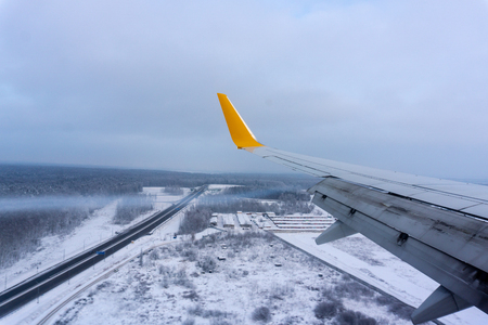 Snow covered land and cloud seen through window, airplane full flaps wing from window