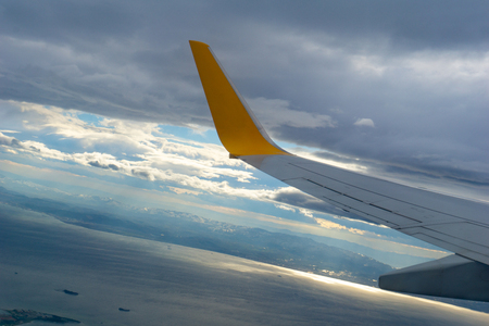 Aerial view of blue sky and cloud seen through window, airplane wing from window 写真素材