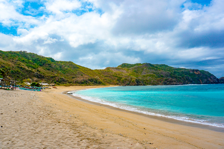 Beautiful scene on best desert beach with white sand, clear water on ocean bay Mawun in tropical island Lombok. Boundless tropic beach with no people in lost paradise. Travel and vacation in Indonesia