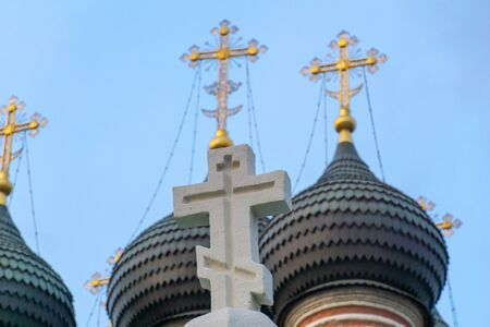 White orthodox church cross with blue sky and sunshine