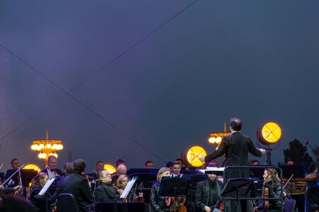 Russia, Moscow, April 30, 2019: Conductor directing symphony orchestra with performers on background night time with light show, VDNH Archivio Fotografico