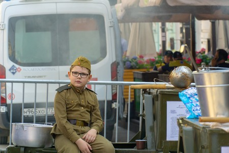 MOSCOW, RUSSIA - MAY 9, 2019: Immortal regiment procession in Victory Day. A soldier child looking at camera posed while sitting with a indifferent face