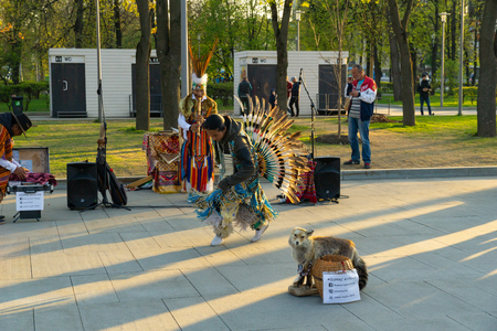 Moscow, Russia, April 30, 2019: A group of Native American Indians in national costumes dancing and singing on the street. 報道画像