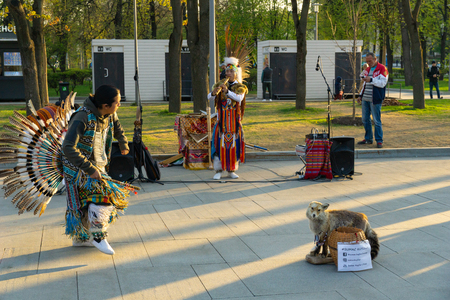 Moscow, Russia, April 30, 2019: A group of Native American Indians in national costumes dancing and singing on the street. Editorial