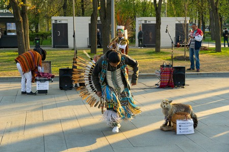 Moscow, Russia, April 30, 2019. A group of Native American Indians in national costumes dancing and singing on the street.