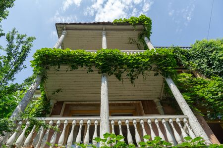 Styled stock photography of the vintage wooden balcony covered with grape leaves. Retro two storey house in mediteranean style useful for photo manipulation artwork. Banque d'images