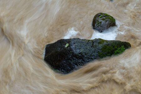 Water rushing by a rock in a river forming a smooth, abstract, painted appearing pattern.
