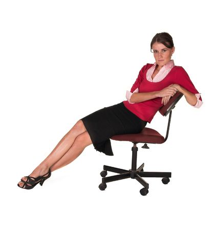 Professional young white lady leaning back in office chair, red sweater, pink top looking at the camera. White isolated back ground. Stock Photo