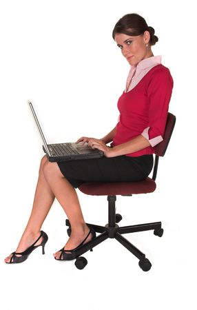 Professional young white lady sitting in office chair typing on notebook laptop, red sweater, pink top looking at the camera. White isolated back ground.