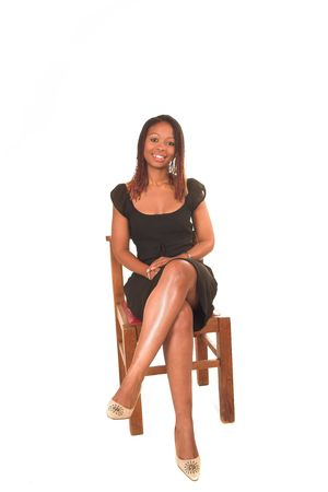Professional young black South African lady business woman in black dress sitting on chair and smiling. White isolated background. Stock Photo