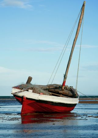 Red and White Sailing boat stranded at low tide in ocean at Vilanculos, Mozambique