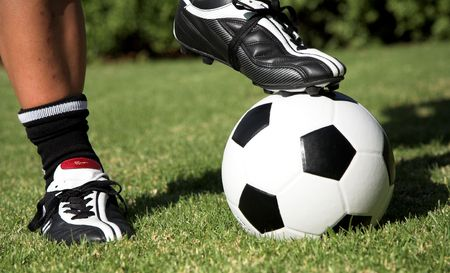 Man standing with one soccerboot on top of the soccer ball and another foot next to the football. Soccer worldcup promotion Stock Photo