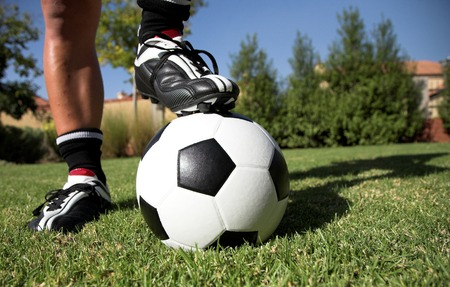 togs: Man standing with his foot soccerboot on the soccer ball in his back yard. Stock Photo
