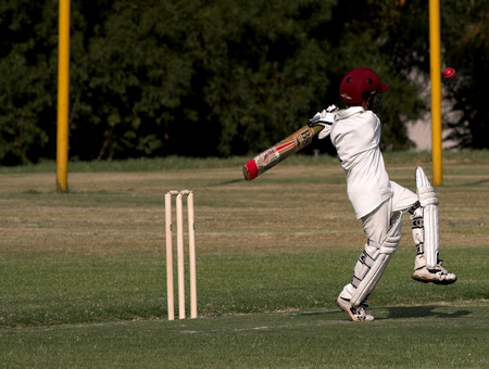 Young boy pulling or hooking a cricket ball during a match. Ball in the air, caught in motion Stock Photo