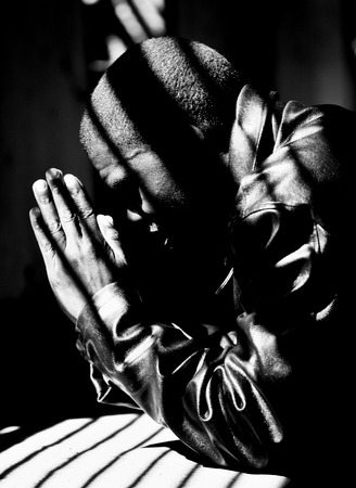Young man praying for the safety of his country, Zimbabwe. Kneeling down, hands together.