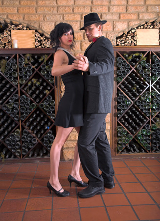 Couple doing the tango down in the old wine cellar, bottles of wine and old stone wall.