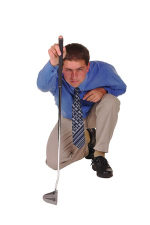 Professional Man in Blue Shirt with Black Tie standing on knee focussing and concentrating over putter. Stock Photo