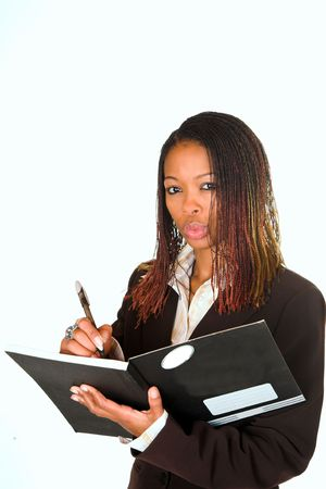 Young black lady, standing writing in black notebook whilst looking at the lense. some copy space Stock Photo