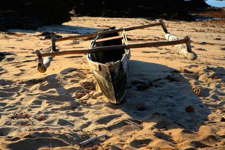 dugout: A dugout canoe boat dhow resting on the beach