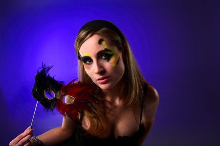 blonde lady holding a mask at the ballroom dance