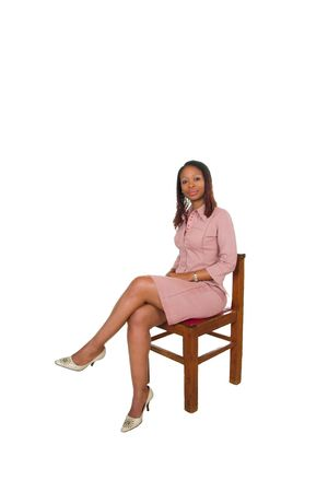 A South African professional business woman dressed in pink dress sitting on a chair