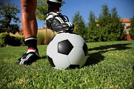 Soccer Boot and Studs Standing on Black and White Football on grass, black and white socks.