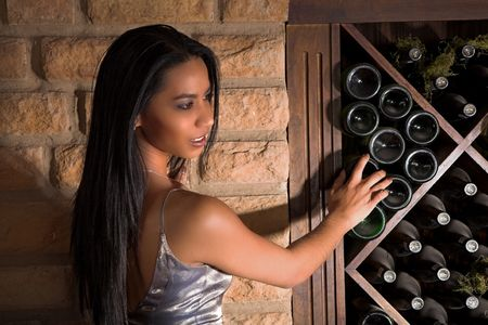 Indian lady standing facing the cellars stone wall, surrounded by shelves containg bottles of red wine.