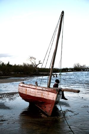 Young boy sitting on a dhow fishing boat sailing boat, witing for his dad to return from the ocean with the days catch. Stock Photo