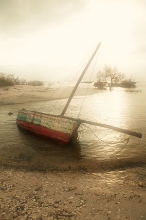 Dhow sailing and fishing boat lying on its side on the beach on an early misty morning Stock Photo