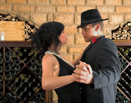 Couple doing the tango down in the wine cellar, getting very close to each other in the dance. True affection and passion.