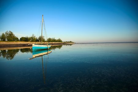Mozambique: A landscape view of the ocean at Pemba, Mozambique with a dhow in the left corner of the image
