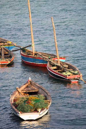 Dhow fishing sailing boats all tied together and floating in a straight line in habour of Pemba, Mozambique.