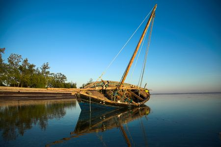 Dhow lying on its side at low tide in the warm paradise waters of Pemba, Mozambique, tropical.