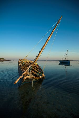 Two dhows waiting in the water during low tide.