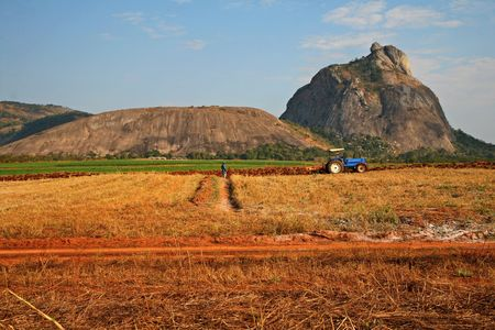 Farmers ploughing the fields with their tractor with a beautiful mountain as a backdrop