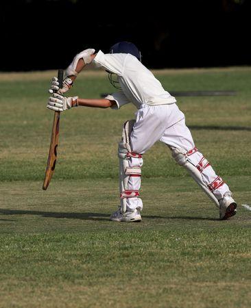 young boy playing a forward defensive cricket shot.