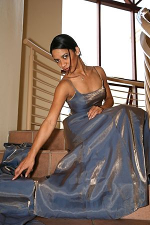 Gorgeous East Indian lady sittiing on the steps in her shiny evening dress Stock Photo