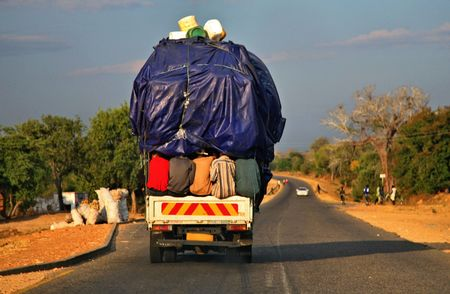 transporting: An overloaded truck transporting people as well as goods across Malawi in Africa. Very humorous picture.