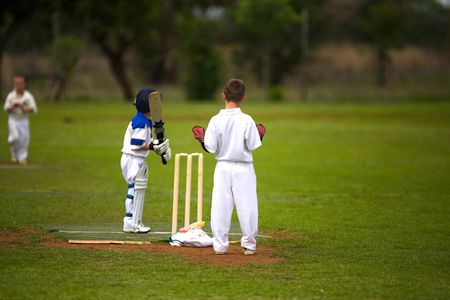 but: nine year old boys playing cricket, bowler running in but keeper is not focused on the game.