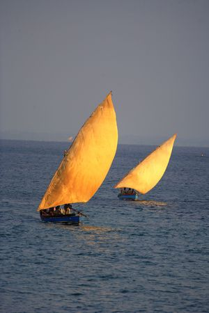 two traditional sailing fishing boats called dhows sailing on the ocean next to each other.