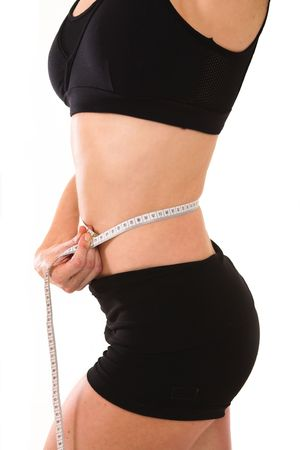 Middle aged lady in her late thirties measuring her waist with a tape, she is very happy with her achievement. Stock Photo - 2710641