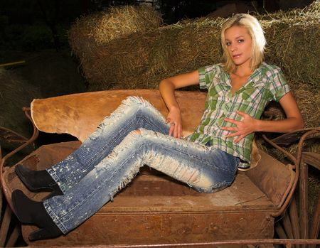 barn boots: a blond lady is sitting sideways on a horse drawn cart in the stables.